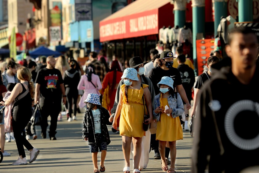 LOS ANGELES, CALIF. - MAR. 21, 2021. A crowd of people descends on Venice Beach, with some wearing masks and others not, on Sunday, Mar. 21, 2021, during the first weekend after coronavirus restrictions were eased in Los Angeles County. (Luis Sinco/Los Angeles Times)