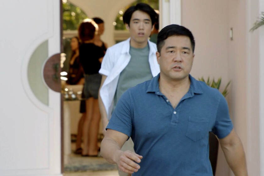 Two men walk out of a house in a scene from a TV show.