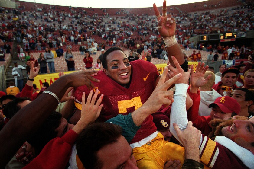 USC's Chad Morton is carried on the shoulders of fans after rushing for 143 yards in the Trojans' victory over UCLA at the Coliseum on Nov. 21, 1999.