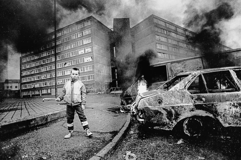 """A boy stands by a flaming car outside Divis flats in Belfast in an image from Patrick Radden Keefe's """"Say Nothing: A True Story of Murder and Memory in Northern Ireland,"""" which documents the violence during """"the Troubles."""""""
