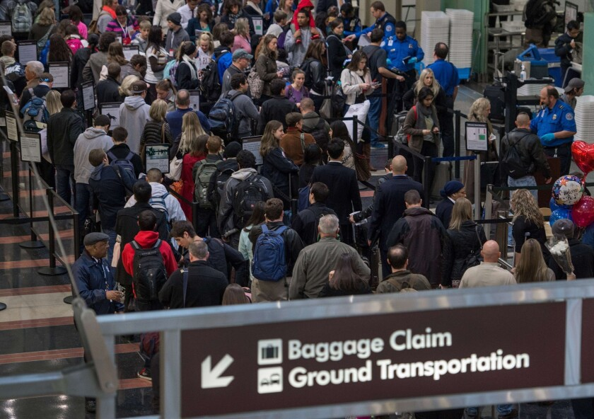 Holiday travelers line up for one of the TSA security checkpoints at Ronald Reagan National Airport in Washington.