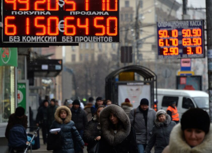 Pedestrians walk under a board listing foreign currency rates against the Russian ruble in central Moscow on Monday.
