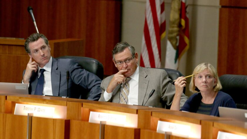 California Lt. Gov. Gavin Newsom, left, California State University Chancellor Timothy P. White, center, and Chairwoman Rebecca Eisen listen during a Board of Trustees meeting at the CSU chancellors office in Long Beach in July.