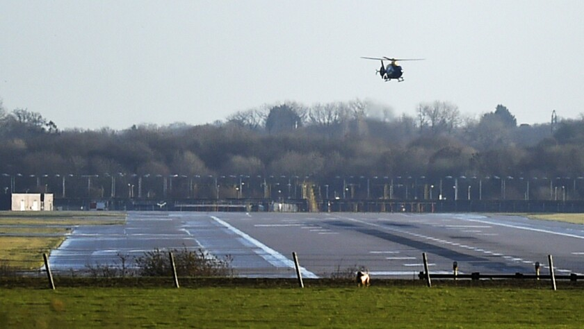 A police helicopter flies over the runway at Gatwick Airport in London. The airport remained closed after drones were spotted over the airfield Wednesday night and Thursday morning.