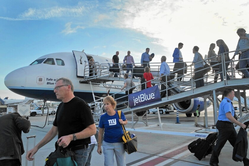 Passengers from New York arrive on a JetBlue plane at Long Beach Airport.