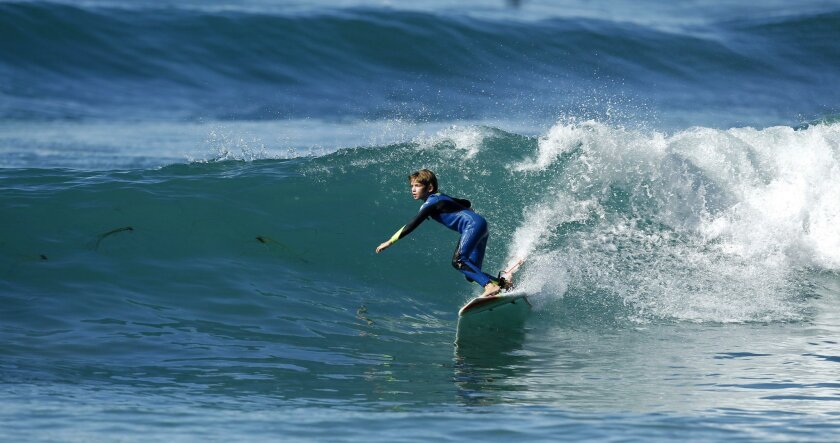Dane Morris, 8, rides a wave at Swami's in Encinitas. Morris is a top ranked surfer in his age bracket in the Western Surfing Association. | (K.C. Alfred/ San Diego Union-Tribune