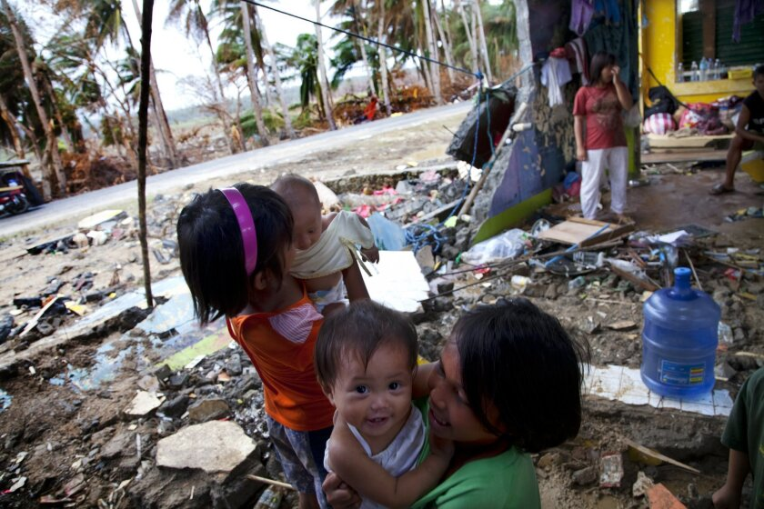 Families take refuge from the near-constant rain falling in Hernani, Philippines in the aftermath of Typhoon Haiyan.