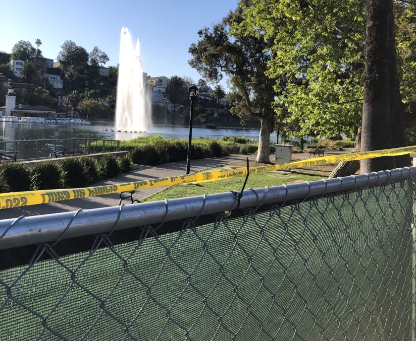 A green fence surrounds Echo Park Lake, with the lake's fountain visible in the distance.
