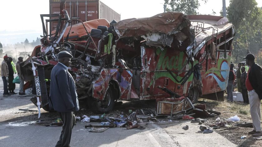 People view the wreckage of a bus and truck that collided near Nakuru, Kenya, on Sunday.