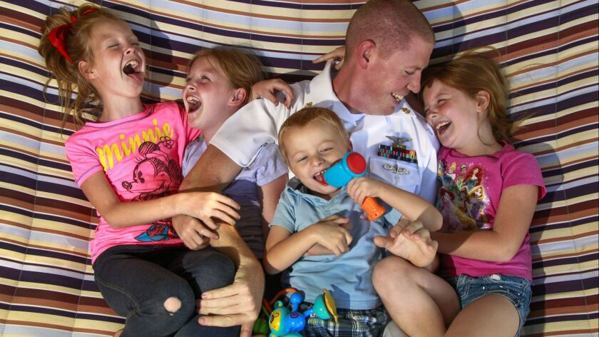 Navy Chief Petty Officer Johnathon Stone, now 32, photographed in a backyard hammock in June 2017 with his children, from left, twins Allison and Alyssa, son Jackson and daughter Madelynn.