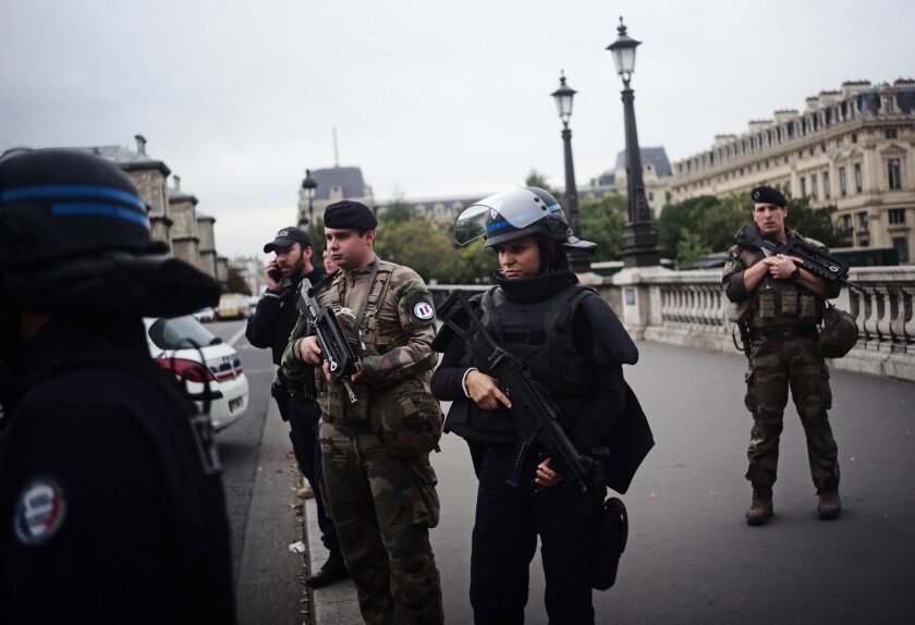 Police officers and soldiers at the scene of an attack at police headquarters in Paris on Thursday.