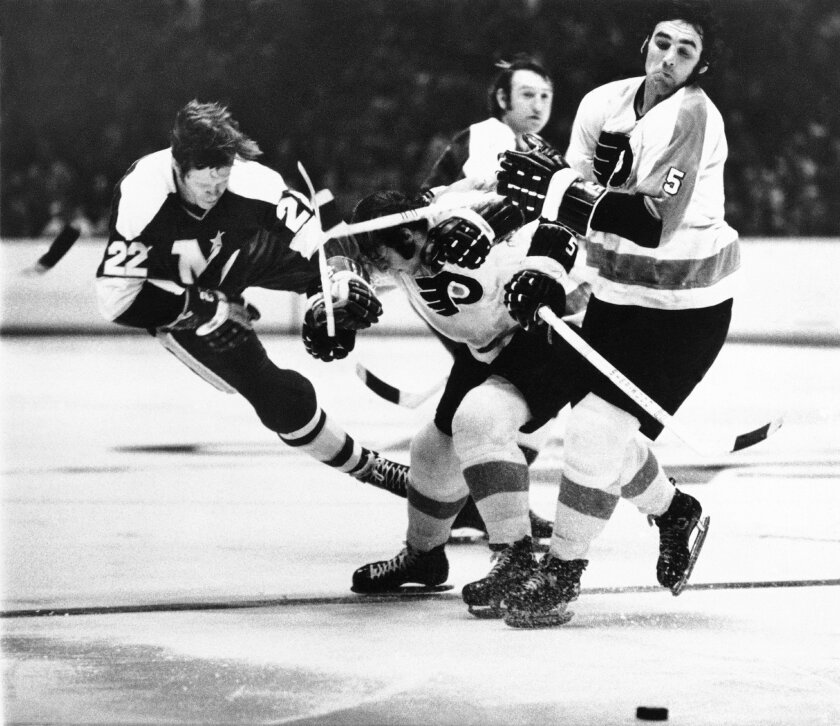 FILE - In this March 2 1972, file photo, Minnesota North Stars' Dennis Hextall (22)  flips over the back of Philadelphia Flyers Bill Brossart , center, during the first period of an NHL hockey game in Philadelphia. Fifty years ago this week, the owners of the so-called Original Six unanimously appr