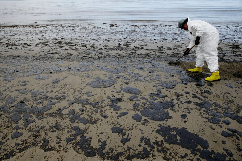 A worker removes oil from the beach at Refugio State Beach, north of Goleta, Calif., Thursday, May 21, 2015. More than 7,700 gallons of oil has been raked, skimmed and vacuumed from a spill that stretched across 9 miles of California coast, just a fraction of the sticky, stinking goo that escaped from a broken pipeline, officials said. (AP Photo/Jae C. Hong)