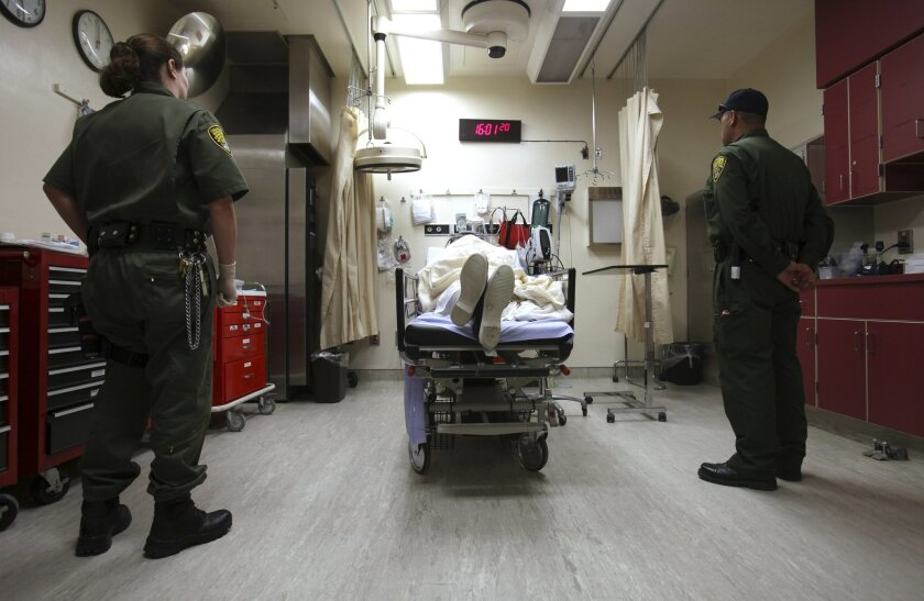 FILE - In this Jan. 14, 2009, file photo, correctional officers stand watch over an inmate receiving treatment in the emergency room at California State Prison, Corcoran, in Corcoran, Calif. U.S. District Court Judge Thelton Henderson has outlined a plan for California to end nearly a decade of federal control of its prison health care system, Tuesday, March 10, 2015. (AP Photo/Rich Pedroncelli, File)
