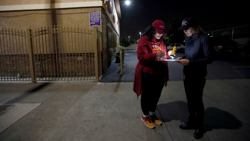 Yasmin Scott-Halcromb, left, and Sarah Mahin consult their map in South Los Angeles during the 2017 homeless count.