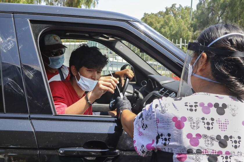 Jorge Angel Llamas, left, takes a COVID-19 test under the supervision of nurse Karen Barringer in Chula Vista on Friday.