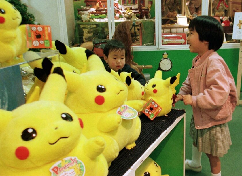 """FILE - In this Dec. 18, 1997 file photo, a girl and her brother view dolls of a Pokemon cartoon character at a toy shop in Tokyo's Ginza shopping district. A survey shows about 90 percent of adults who have downloaded the new """"Pokemon Go"""" smartphone game in 2016, which lets you find cartoon monster"""