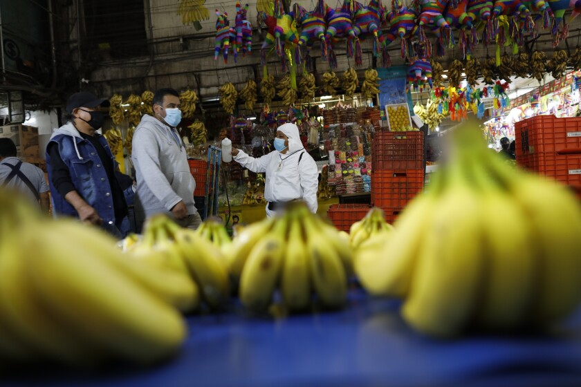 A worker wearing a protective suit offers antibacterial hand gel to passing shoppers and workers to curb the spread of the new coronavirus, inside the Central de Abastos, the capital's main market, in Mexico City, Tuesday, Dec. 8, 2020.(AP Photo/Rebecca Blackwell)
