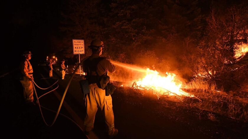 Firefighter Shawn Lee, right, and his colleagues try to contain flames from the Carr fire as it spreads toward the town of Douglas City near Redding on July 30.