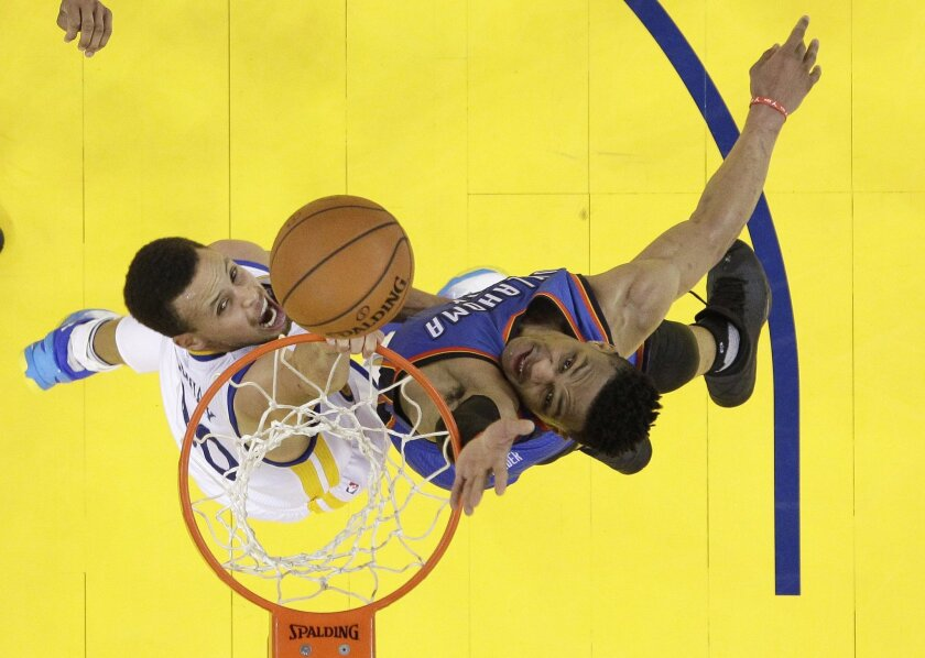 Golden State Warriors' Stephen Curry, left, drives to the basket as Oklahoma City Thunder's Russell Westbrook defends during the second half in Game 7 of the NBA basketball Western Conference finals Monday, May 30, 2016, in Oakland, Calif. Golden State won 96-88. (AP Photo/Marcio Jose Sanchez)