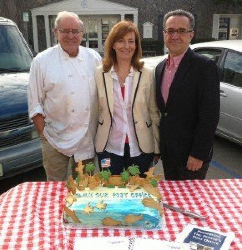 Francois Goedhuys of Girard Gourmet (left) poses next to the cake he baked for the rally. With him are Post Office Task Force members Leslie Davis and Joe LaCava.