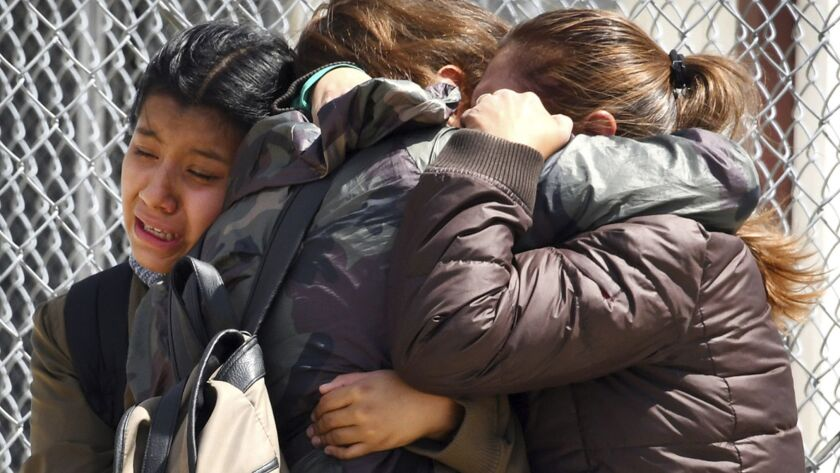 Student Melany Aquino, center, is embraced by her younger sister, Halie, 11, left, and mother, Victo