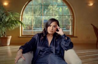 Demi Lovato wearing a silk outfit, sitting in a white armchair