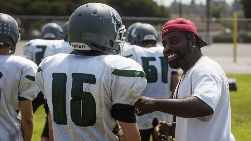 Brethren Christian's head coach Leon Green jokes with Slater Jones during practice in Huntington Bea
