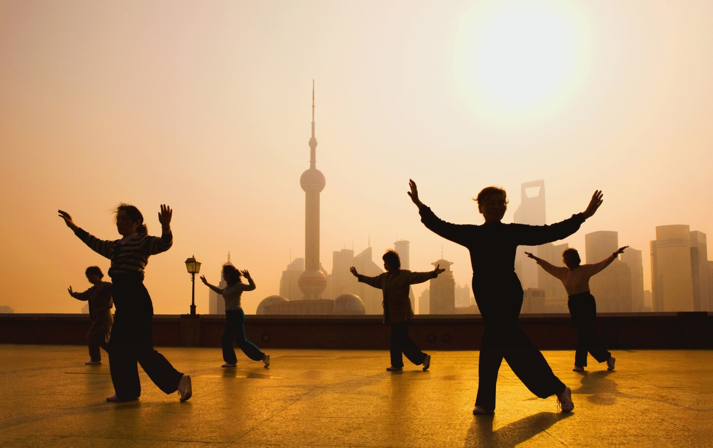 People gather to practice movements on the Bund, with the Shanghai skyline in the background.
