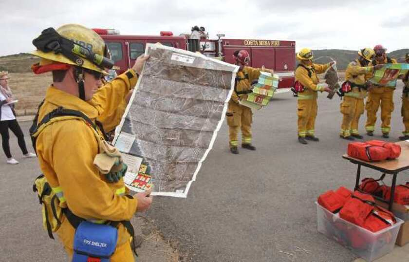 Newport Beach firefighter Justin Keene, left, examines a pre-plan map that outlines information about hydrants and station areas vital to fighting a wildfire similar to the Laguna Beach firestorm in 1993.