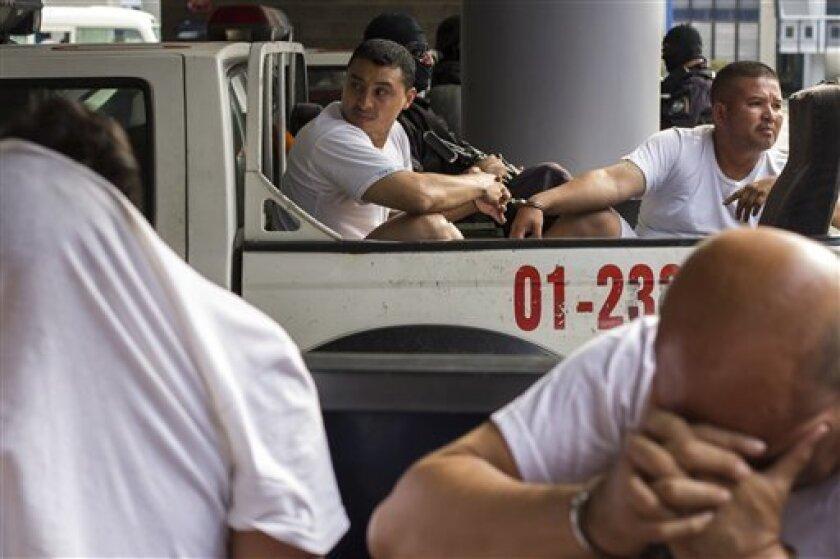En esta imagen del martes 2 de agosto de 2016, Marvin Quintanilla Ramos, a la izquierda, un pastor evangélico al que la policía de El Salvador acusa de ser el financista de la Mara Salvatrucha, es trasladado de vuelta a prisión esposado a otro preso en la parte trasera de una camioneta descubierta de la policía tras una vista judicial en San Salvador, El Salvador. Pandillero operaba como pastor