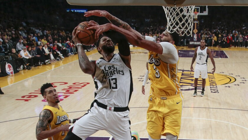 Lakers forward Anthony Davis blocks a shot by Clippers forward Paul George during their game Dec. 25, 2019.