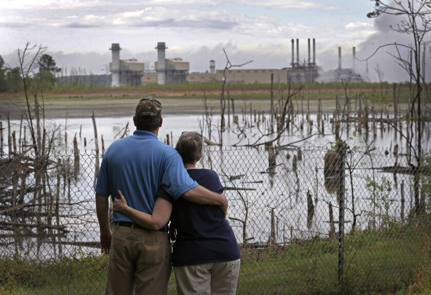 Bryant and Sherry Gobble look from their yard across an ash pond full of dead trees toward Duke Energy's Buck Steam Station in Dukeville, N.C., on April 25, 2014.