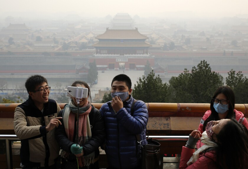 Visitors, some wearing masks to protect themselves from pollutants, share a light moment as they take a selfie at the Jingshan Park on a polluted day in Beijing, China, on Dec. 7, 2015.