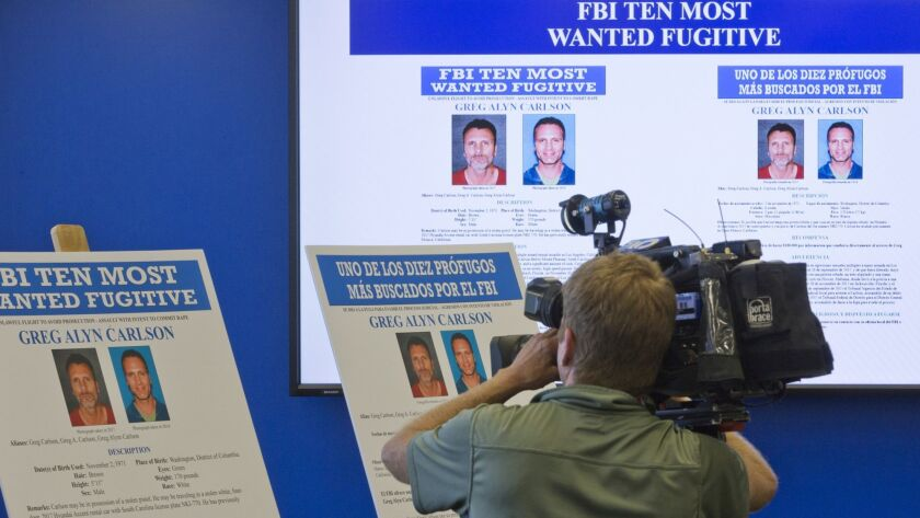 A television cameraman films the photographs of Greg Alyn Carlson during a news conference at the FBI headquarters in Los Angeles.