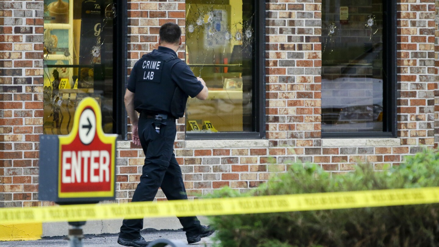 """A crime lab technician walks past bullet-riddled windows at a Wendy's restaurant in Omaha on Wednesday. Police say a robber was killed by officers Tuesday night, along with a crew member of the """"Cops"""" television show."""
