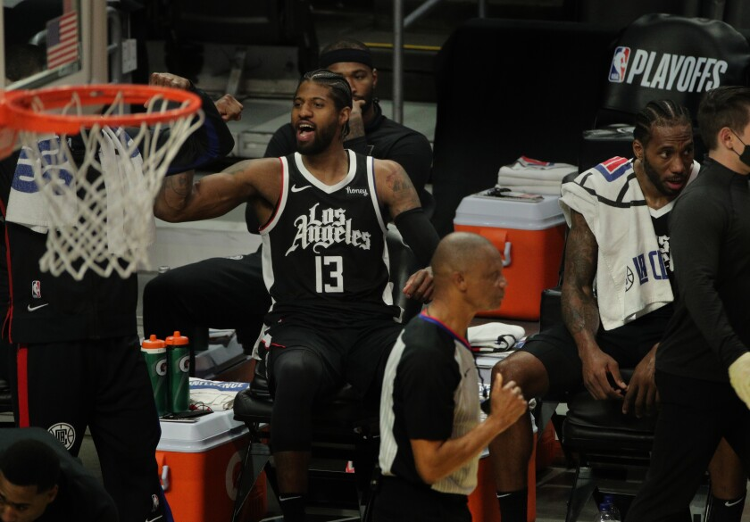 The Clippers' Paul George (13), seated next to Kawhi Leonard, cheers toward the end of the win over Utah on June 12, 2021.