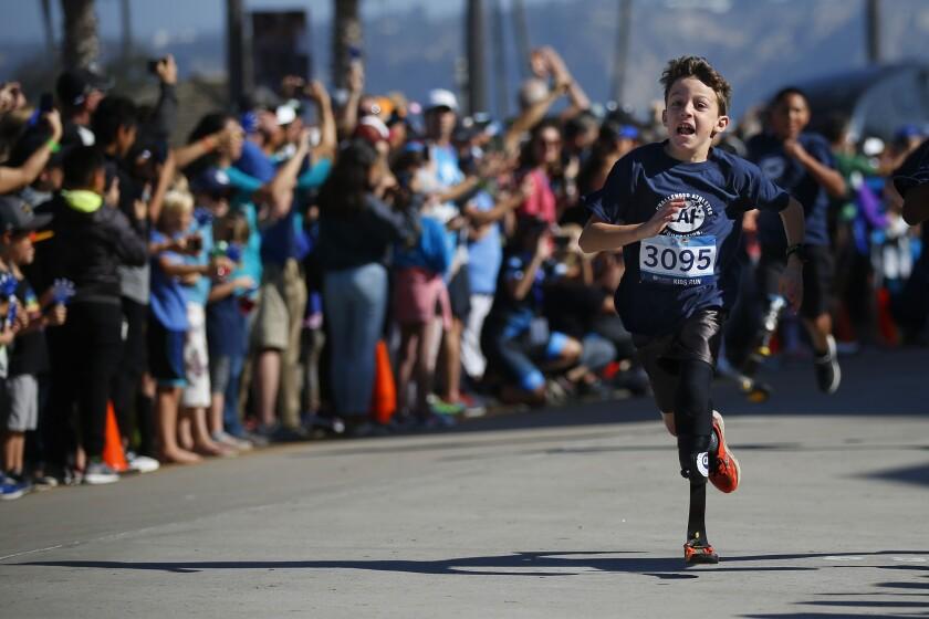 Logan Seitz, wearing bib No. 3095, ran in the Kid's Run during the Challenged Athletes Foundation San Diego Triathlon Challenge in La Jolla on Sunday.