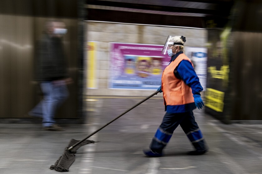 An employee wearing face masks and gloves to protect against the COVID-19 coronavirus cleans a floor at a subway station in Kyiv, Ukraine on Monday, June 1, 2020. Ukraine continued to ease its coronavirus restrictions Monday, lifting a ban on intercity travel and allowing gyms and swimming pools to reopen. (AP Photo/Evgeniy Maloletka)