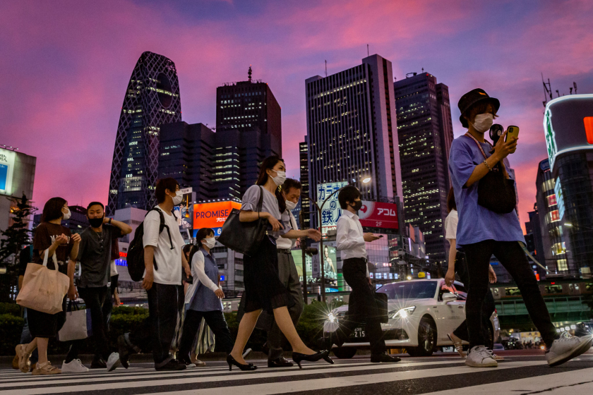 People wearing face masks cross a city street at dusk with skyscrapers in the background.