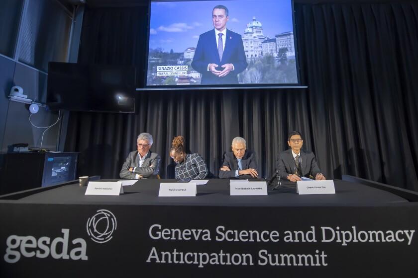 Patrick Aebischer, GESDA Vice Chairman, Nanjira Sambuli, Policy Analyst and Advocacy Strategist, Kenya, Peter Brabeck-Letmathe, GESDA Chairman, Chorh Chuan Tan, Chief Health Scientist, Singapore, left and right, and Swiss Federal Councilor Ignazio Cassis on the screen in recorded video, speaks about the first Geneva Science and Diplomacy Anticipation Summit 2021 (GESDA), during a press conference at the Campus Biotech in Geneva, Switzerland, Thursday, October 07, 2021. (Martial Trezzini/Keystone via AP)