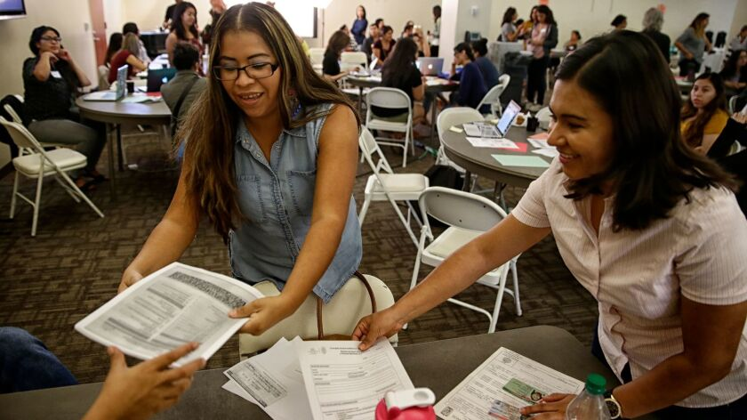 Vianey Romero, left, sorts renewal documents with Nohemi Martinez of the Mexican Consulate during a