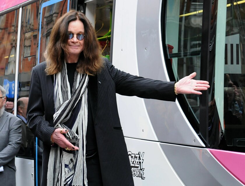 Rock star and former Black Sabbath vocalist  Ozzy Osbourne, right, launches a Midland Metro tram bearing his name, on a newly-opened route in Birmingham central England Thursday May 26, 2016. (PA via AP) UNITED KINGDOM OUT