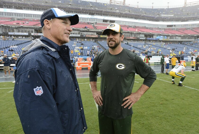 Tennessee Titans head coach Ken Whisenhunt, left, talks with Green Bay Packers quarterback Aaron Rodgers in the rain as the teams warm up before a preseason NFL football game Saturday, Aug. 9, 2014, in Nashville, Tenn. (AP Photo/Mark Zaleski)