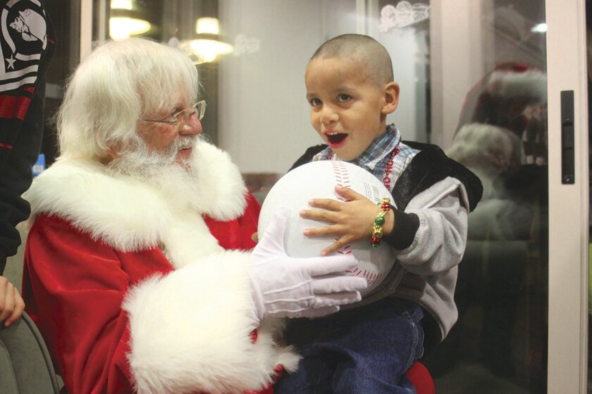 Eduardo, 5, loves his present from Santa Claus at the 13th annual holiday party hosted by La Jolla Cove Suites for homeless children receiving assistance from St. Vincent de Paul, Dec. 6, 2013. This photo by Ashley Mackin won an honor from the San Diego Press Club.