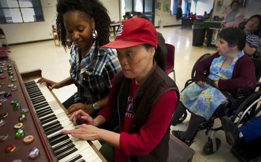 Alise Brown, left, who works with Arc of San Diego, helps Truc Nguyen on the piano. Programs for the developmentally disabled such as this one could face cuts along with an array of other services if state revenues fall short at the end of the year. .