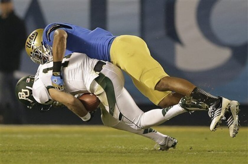 Baylor quarterback Nick Florence, bottom, is sacked UCLA linebacker Anthony Barr for a 13-yard loss during the first half of the NCAA college football Holiday Bowl game on Thursday, Dec. 27, 2012, in San Diego. (AP Photo/Lenny Ignelzi)
