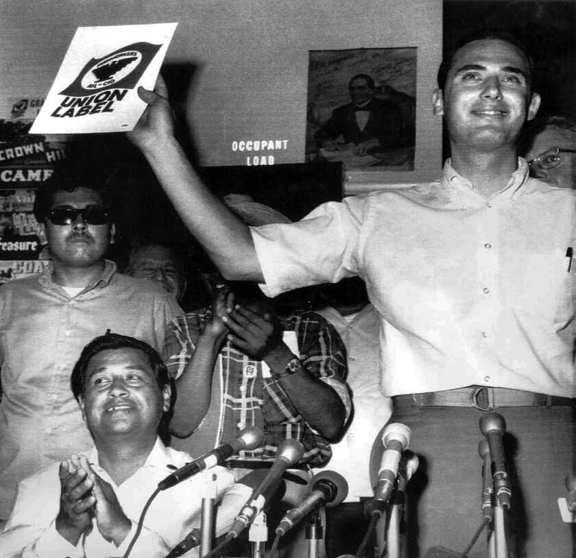 Cesar Chavez (left) applauds as John Giumarra, Jr., whose family owned a table grape vineyard, holds a copy of the Union Label during a meeting of the United Farm Workers in Delano, Calif., in 1970.