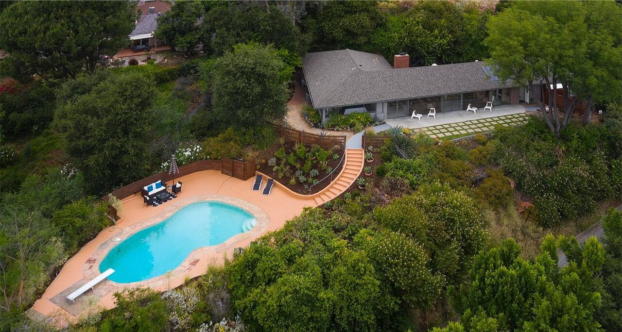 Built in 1952, the stylish home expands to a courtyard with a koi pond, a hillside patio and a swimming pool with a diving board.