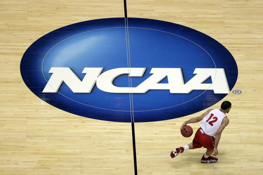 FILE - In this March 26, 2014, file photo, Wisconsin's Traevon Jackson dribbles past the NCAA logo during practice at the NCAA men's college basketball tournament in Anaheim, Calif. A federal judge ruled that the NCAA can't stop players from selling the rights to their names, images and likenesses, striking down NCAA regulations that prohibit them from getting anything other than scholarships and the cost of attendance at schools. U.S. District Judge Claudia Wilken in Oakland, Calif., ruled in favor Friday, Aug. 8, of former UCLA basketball star Ed O'Bannon and 19 others in a lawsuit that challenged the NCAA's regulation of college athletics on antitrust grounds. (AP Photo/Jae C. Hong, File)
